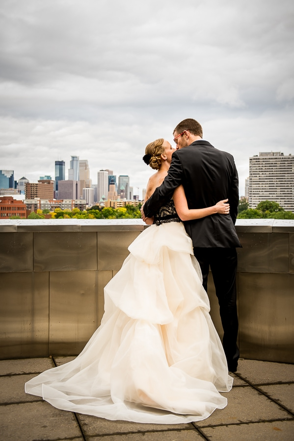The bride and groom share a tender moment and kiss on their wedding day at the Weisman Art Museum with the Downtown Minneapolis skyline in the distance.