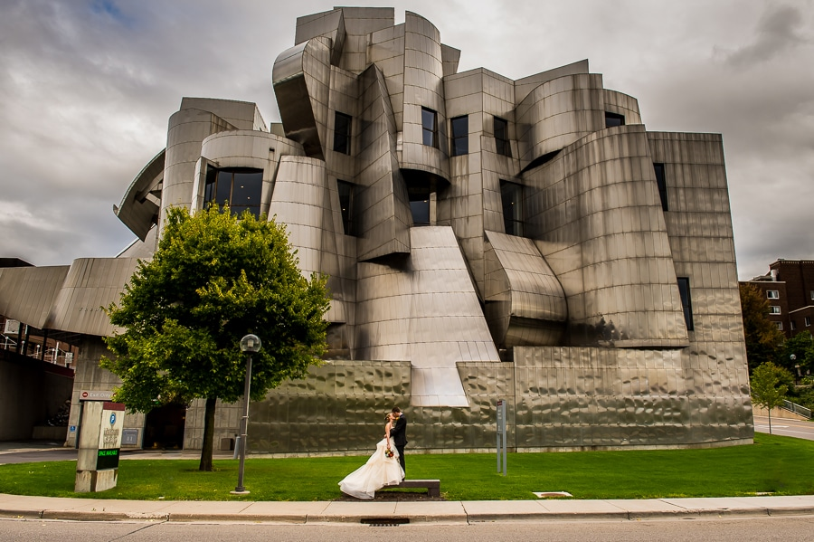 Newly married couple kissing while standing on the bench on front of the Weisman Art Museum on their wedding day