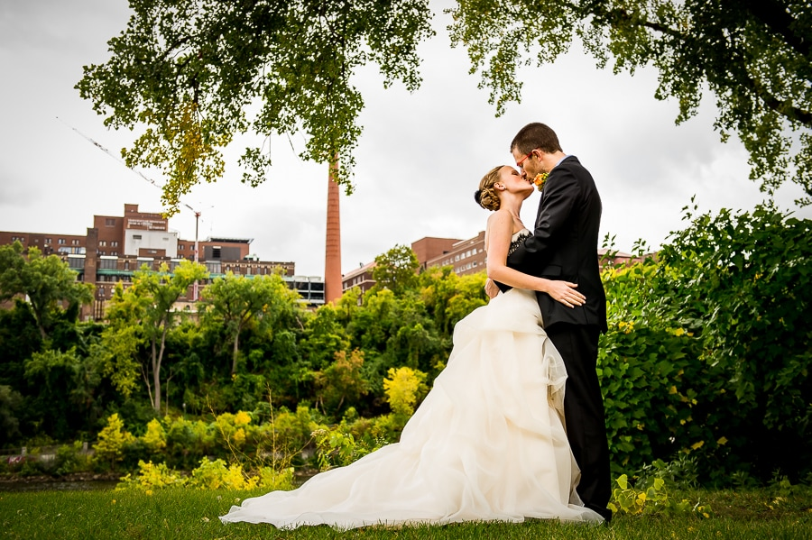 Bride and groom share a kiss on the bank of the Mississippi River during their Weisman Art Museum wedding