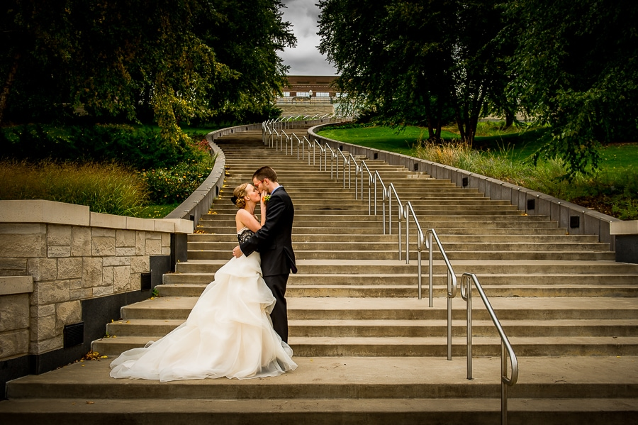 Newlyweds embracing in front of long stairway just up the street from their Weisman Art Museum wedding on the University of Minnesota campus