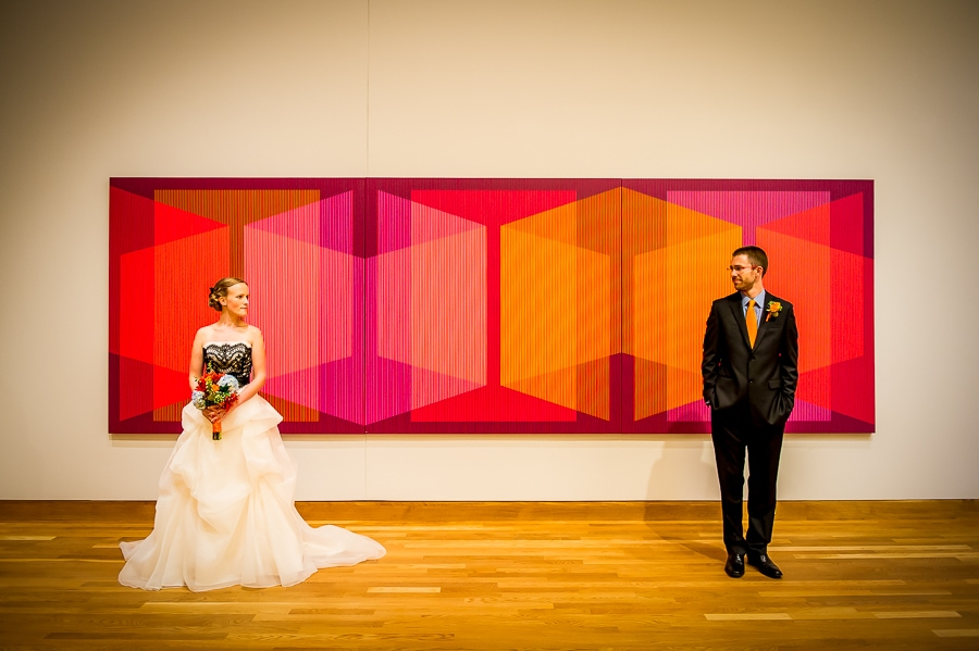 Newly married couple posing in from of large wall art at their Weisman Art Museum wedding