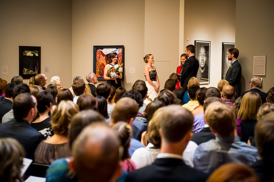 Bride smiles widely at her groom during their wedding ceremony, surround by all the cool artwork, at the Weisman Art Museum