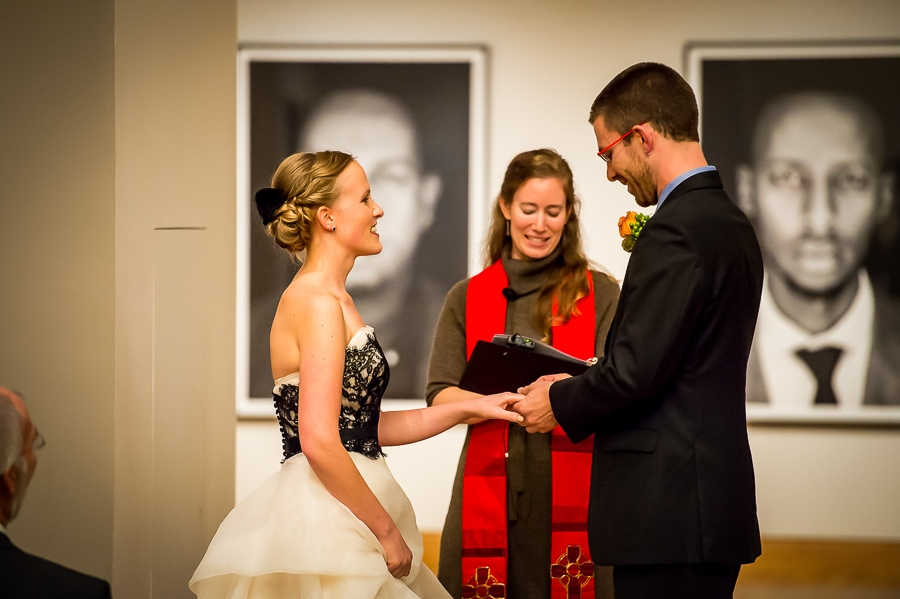 The groom puts the ring on his new bride's finger during their wedding ceremony at the Weisman Art Museum