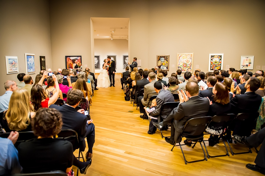 Bride and groom share their first kiss as a married couple during their wedding ceremony at the Weisman Art Museum