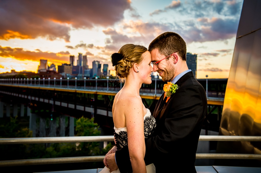 Bride and groom with beautiful sunset sky behind them along with the Minneapolis skyline, as seen from the balcony of the Weisman Art Museum