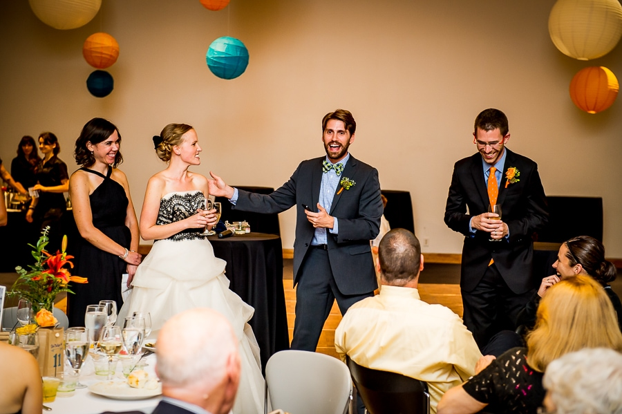 Best man gives his speech next to the bride and groom and maid of honor at a Weisman Art Museum wedding