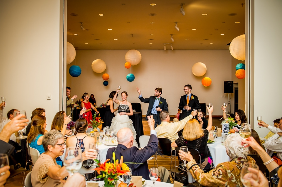 Wide angle wedding reception cheers after the speeches at the Weisman Art Museum