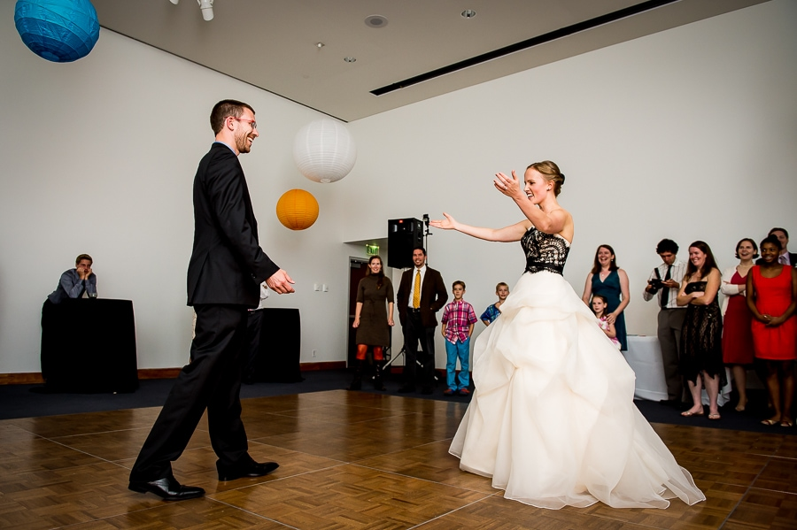 Bride and Groom's approach each other with arms wide open for their first dance as husband and wife during their Weisman Art Museum wedding reception