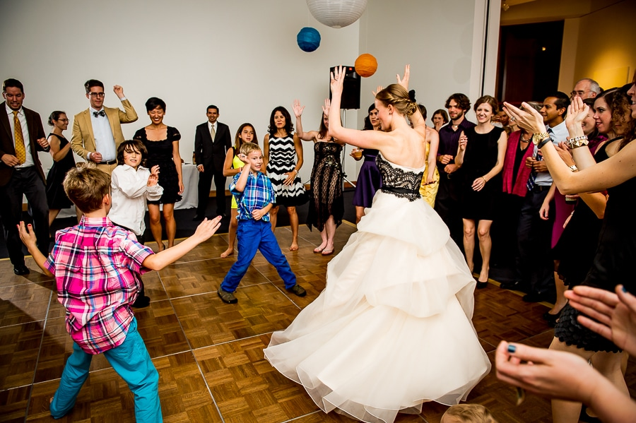 Dance party action shot with bride and young wedding guest in the middle of the dance floor circle at the Weisman Art Museum