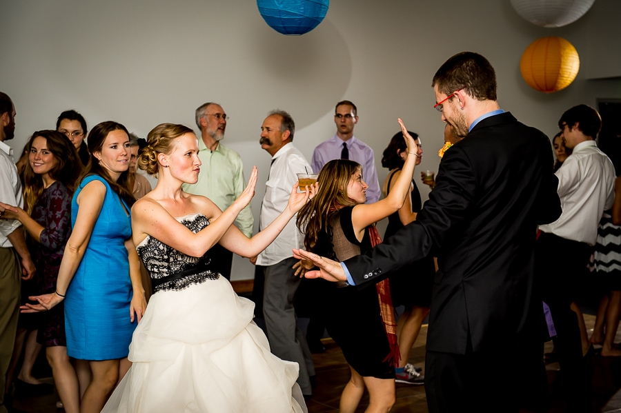Bride and groom dancing with each other and amongst their many wedding guests