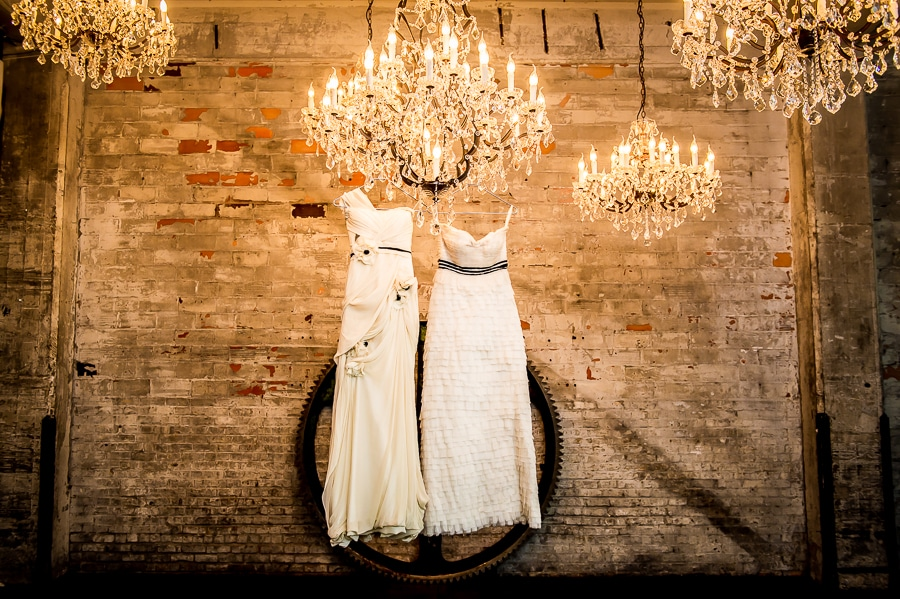 Two wedding dresses hang from the chandelier at Aria during a same sex wedding in Minneapolis