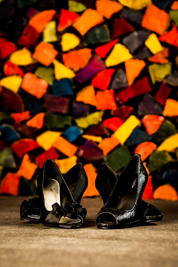 The two brides' wedding shoes in front of a colorfully painted woodpile