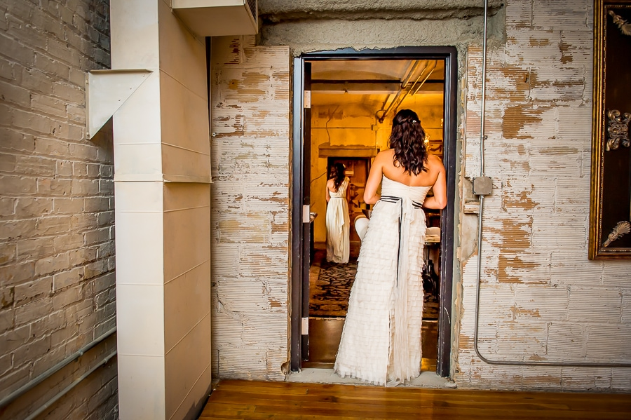 Two brides framed in the doorway right before her first look moment on their same sex wedding day at Aria in Minneapolis