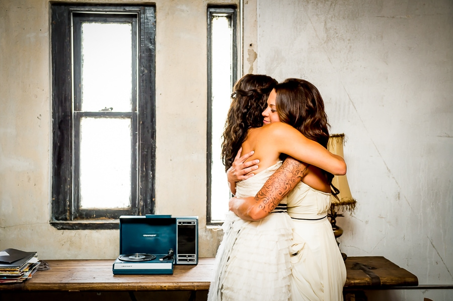 Two beautiful brides hugging each other passionately during their first look at the first ever same sex wedding at Aria in Minneapolis