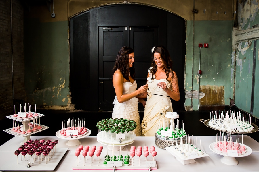 Brides enjoy cake pops during their same sex wedding at Aria