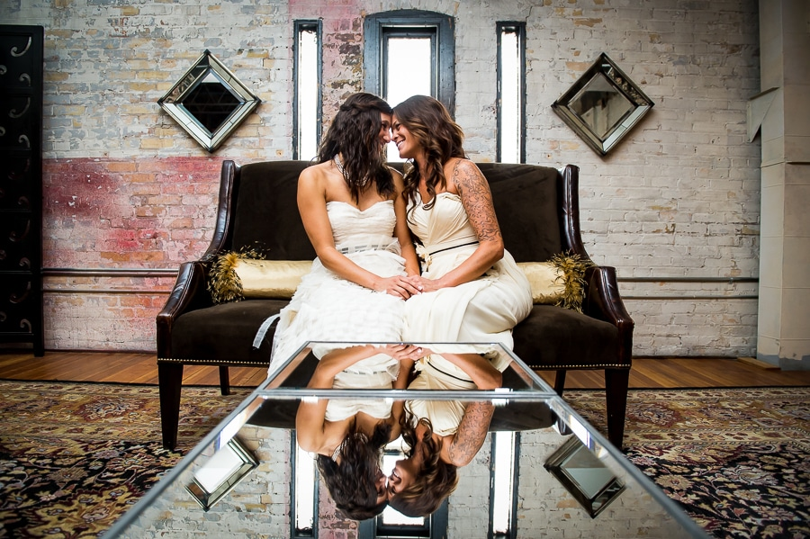 Two brides snuggle up close during their same sex wedding at Aria in the North Loop of Minneapolis