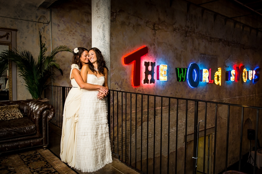 "Two brides cuddling closely in the upper level rooms of Aria with the ""The World is Yours"" sign illuminating behind them"
