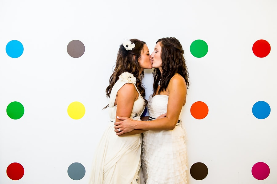 Two brides kiss in front of the polka dot wall at Aria in Minneapolis