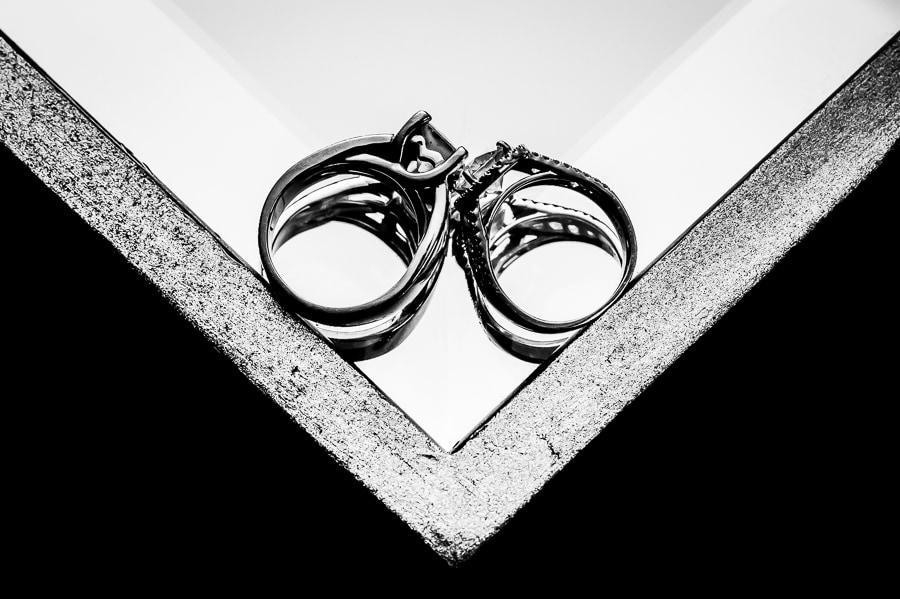 Fine art wedding ring shot with the rings making a v as they rest against each other on a mirror table