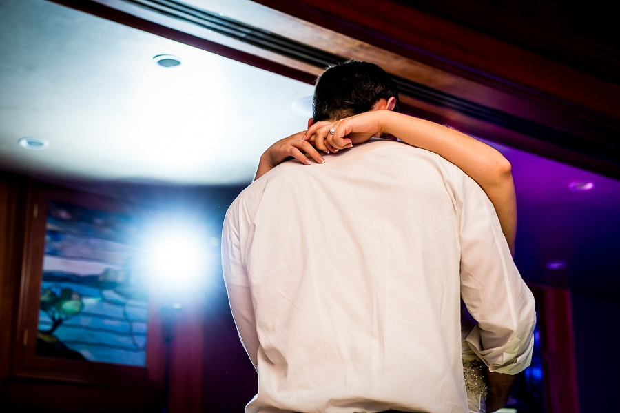 Bride wraps her arms around her groom on the dance floor