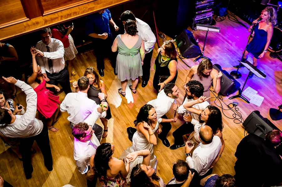 Bride, groom and their wedding guests passionately sing along with the music on the dance floor