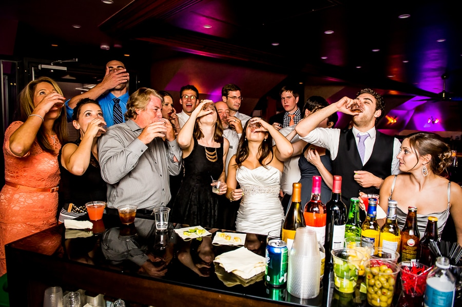 Bride takes shots at the bar with a bunch of her wedding guests