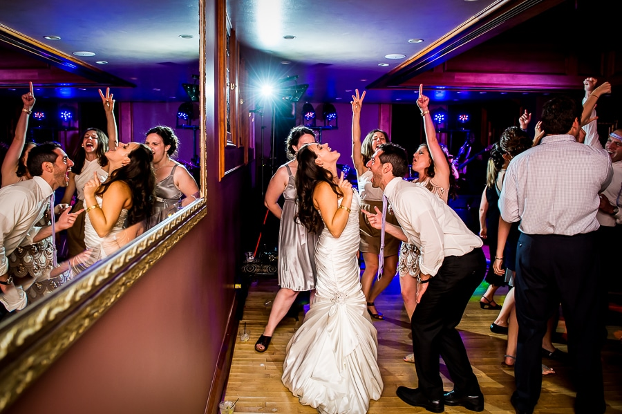 Dynamic and vibrant image of couple signing at the top of their lungs, as their wedding guests join them with their hands high up in the air during their Van Dusen Mansion wedding reception dance.