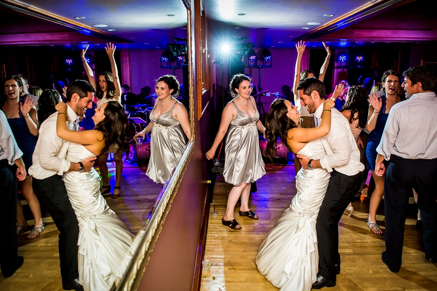 Bride and groom embrace passionately on the dance floor with their image reflected in a large mirror hung on the wall