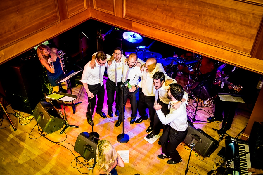 Groomsmen take the stage to sing a song to the bride
