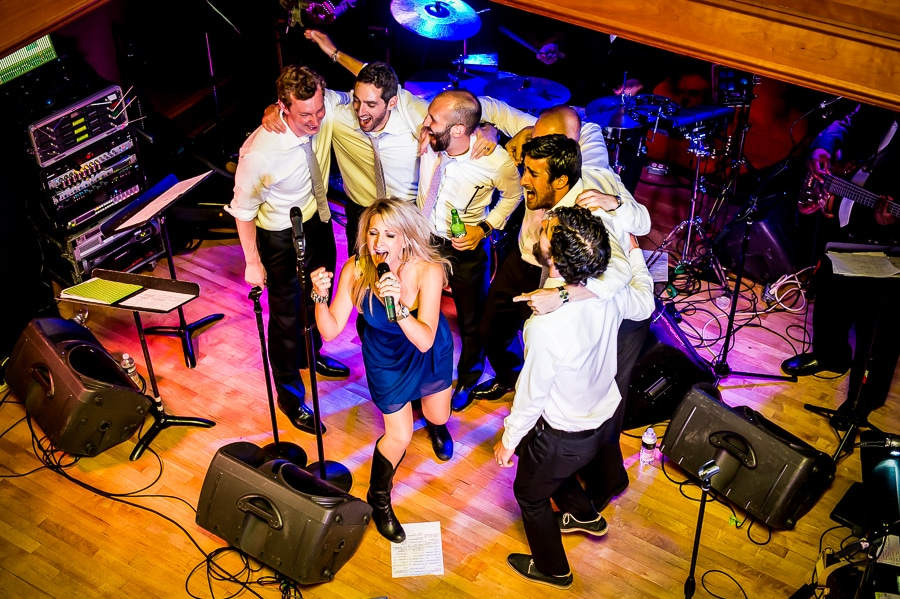 Wedding singer joins the groomsmen on stage to sing together