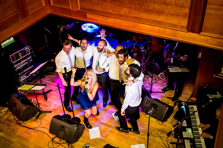 Wedding band singing with the groomsmen, belting out a song at the top of their lungs
