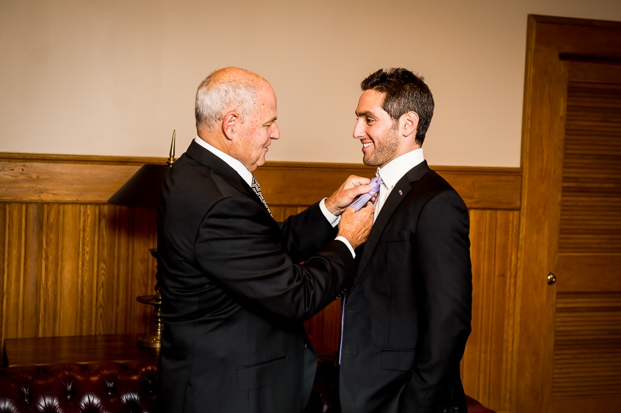 Father of the bride adjusts the grooms tie