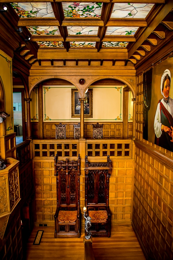 Giant wooden throne chairs on the main Van Dusen Mansion staircase