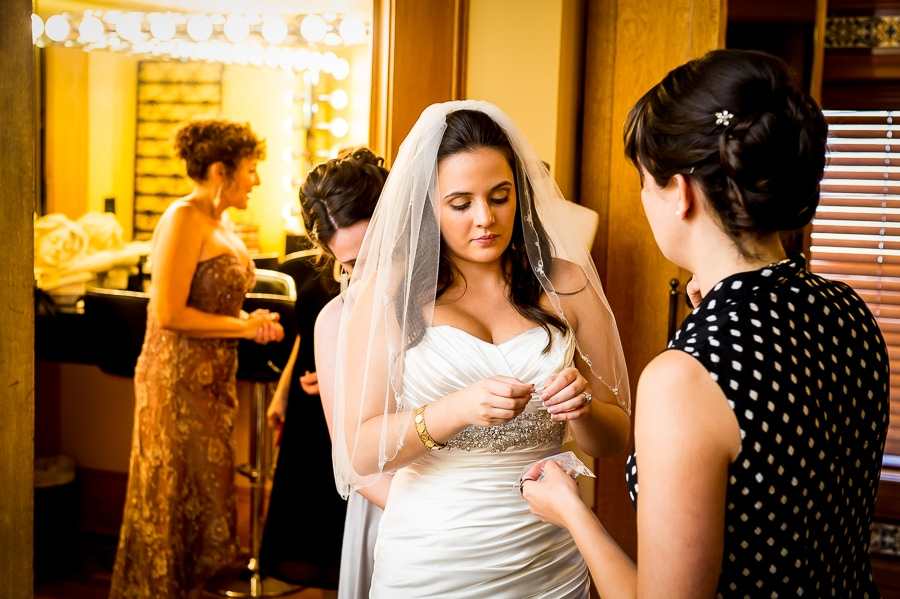 Bride prepares her wedding day earrings in the bridal suite at the Van Dusen Mansion