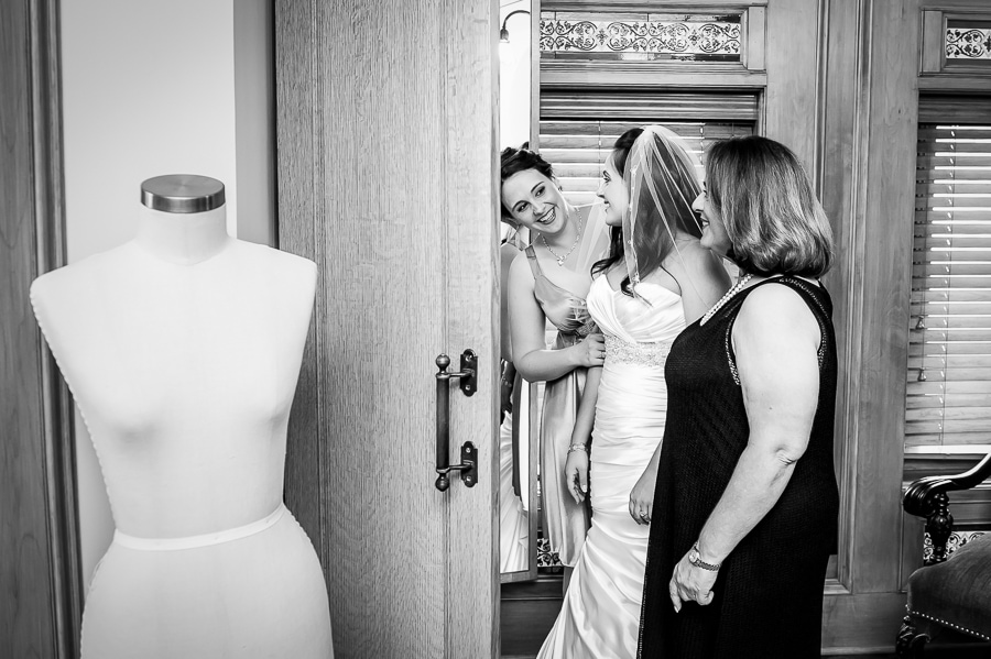 Mother of the bride and maid of honor share a sweet moment with the bride as she gets ready for her jewish wedding at the Van Dusen Mansion