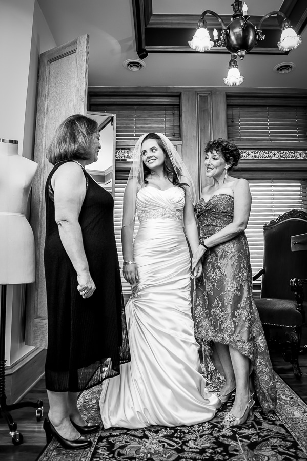 Mother of the bride and the mother of the groom smiling hugely at the gorgeous bride