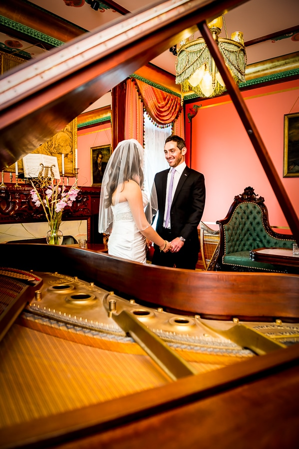 Artistic photo shot thru an open piano of the bride and groom holding hands and smiling on their wedding day at the Van Dusen Mansion