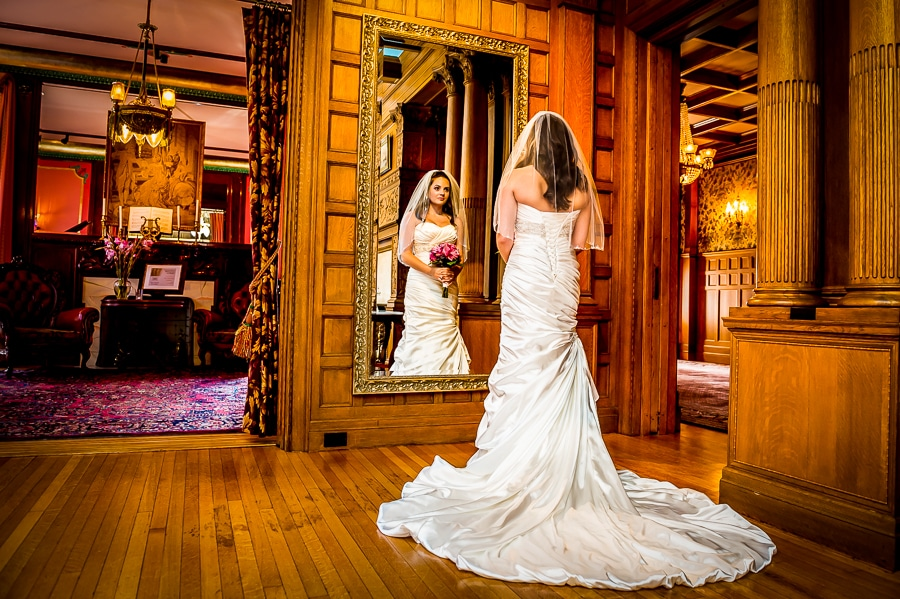 Bride looking at herself, in her beautiful wedding dress, inside the luxurious main foyer during her Van Dusen Mansion Wedding