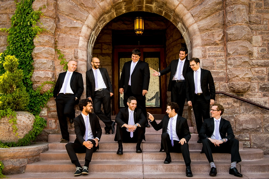Groomsmen acting silly on the large stone steps outside of the Van Dusen Mansion