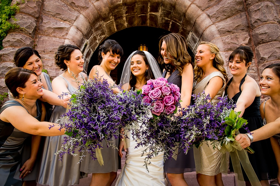 Bride along with her bridesmaids and their beautiful bouquets of flowers under the stone arch near the main entrance of the Van Dusen Mansion