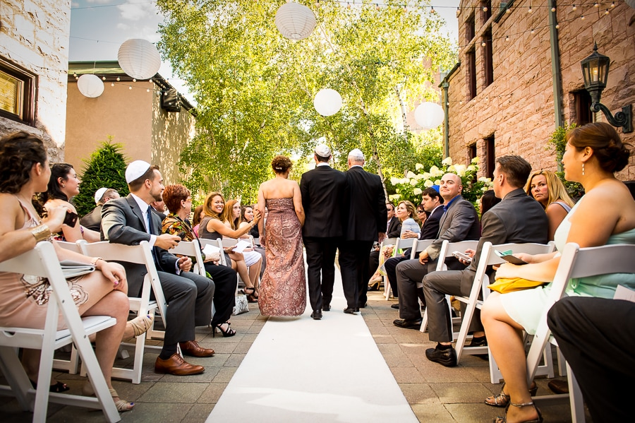 Parents walk the groom down the isle of an gorgeous outdoor wedding ceremony during the summer