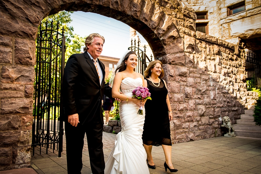 Brides parents walk her down the isle during a beautiful jewish wedding, in the summer, at Van Dusen Mansion