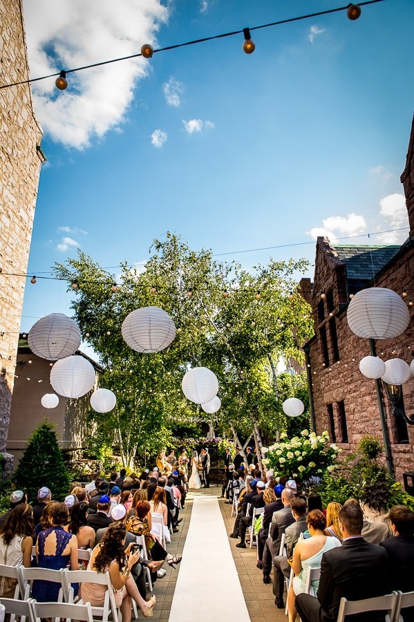 Wide angle vertical shot of the outdoor wedding ceremony space at Van Dusen Mansion on a brilliantly blue skied summer day