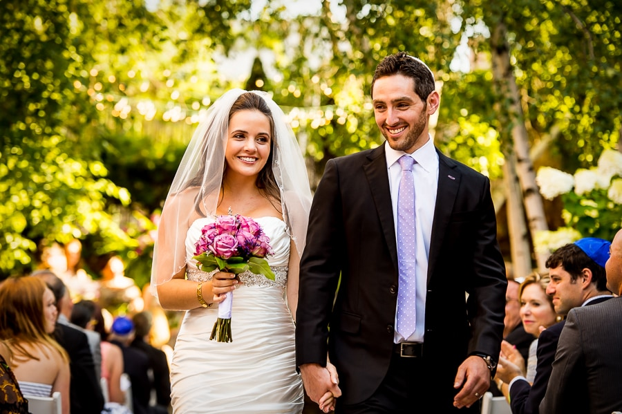 Bride and groom walking back up the isle, with huge smiles on their faces, as newlyweds during their outdoor ceremony at their Van Dusen Mansion Wedding