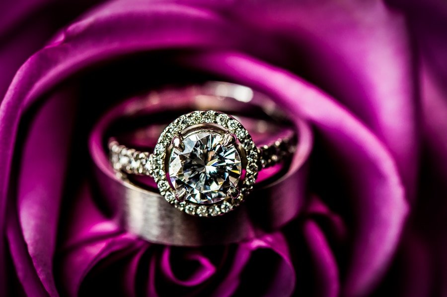 Wedding ring macro shot of the brilliant diamonds sitting inside of a purple rose at the Van Dusen Mansion in Minneapolis