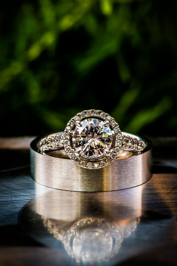 Wedding rings on reflective table with the lush green grounds of the Van Dusen Mansion in a beautiful bokeh.