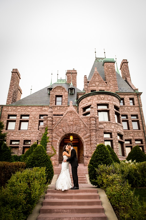 Bride and groom share a kiss on the long stairway in front of the Van Dusen Mansion during their summer wedding