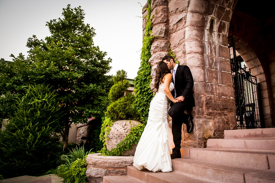 Bride and groom share a kiss while the groom leans up against the giant brick of the arch in front of the Van Dusen Mansion on their wedding day