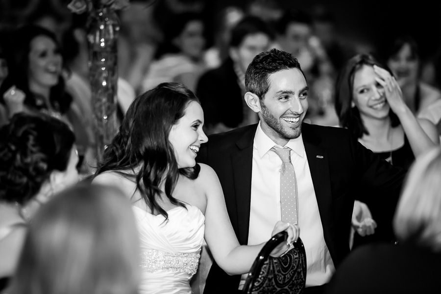 Bride and groom laughing in reaction to best man speech