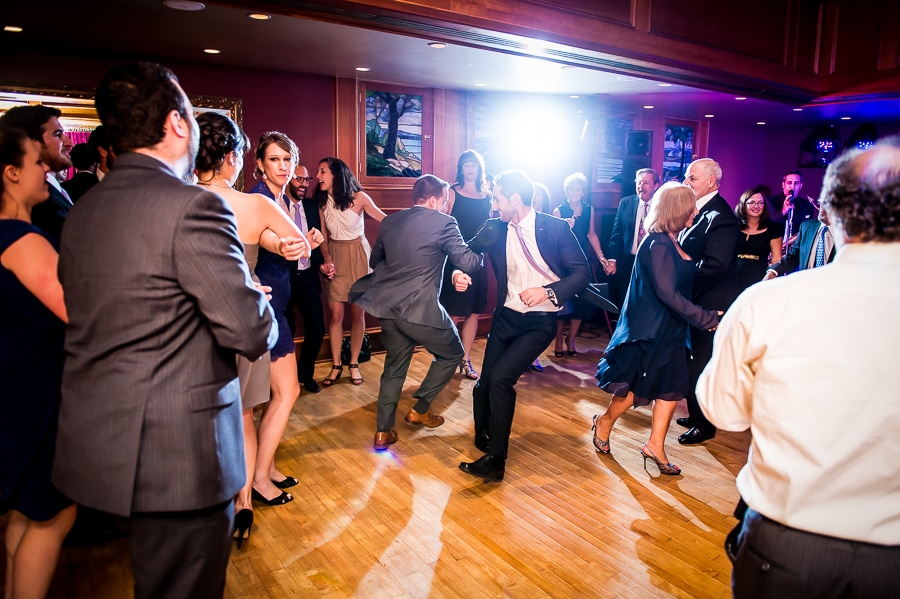 Groom dances energetically with wedding guest